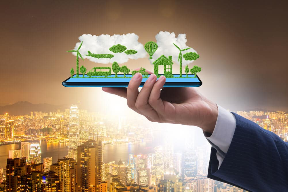 Hand holding tablet with mini ecosystem - Small Energy Bill